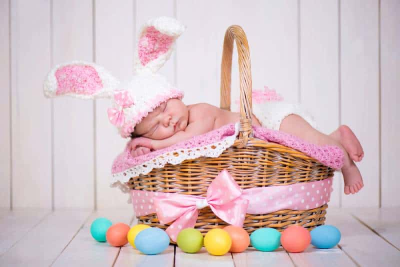 Newborn baby girl in a rabbit costume lying in a basket