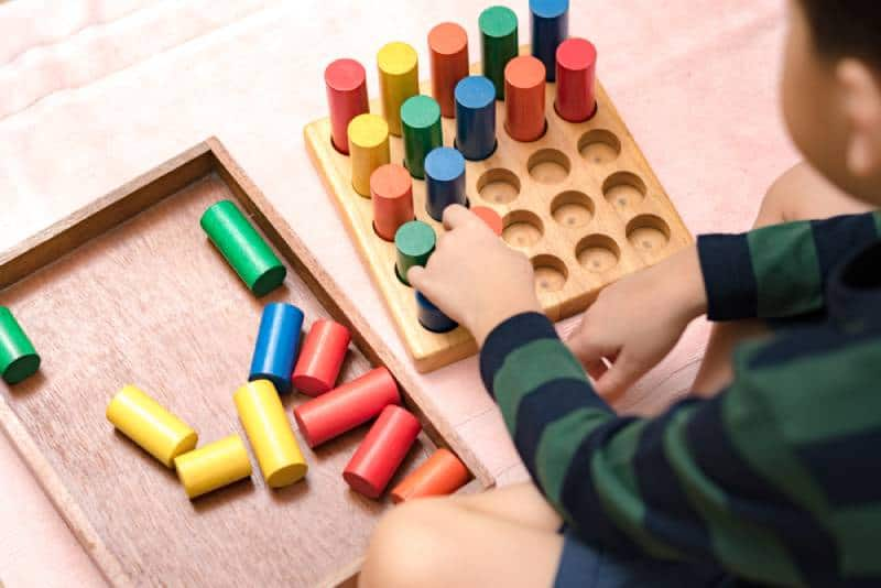 child learning math with wooden sensorial blocks