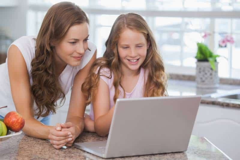 smiling girl and mother using laptop in the house