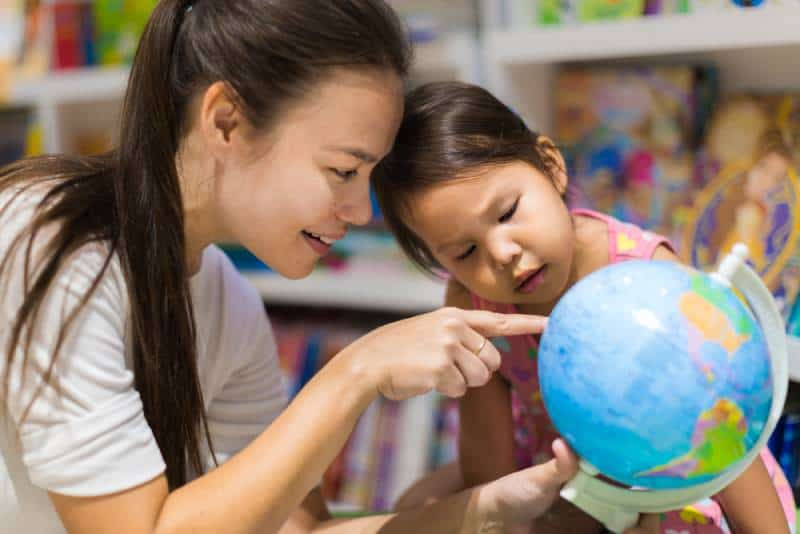 woman and daughter learning geography on a world globe