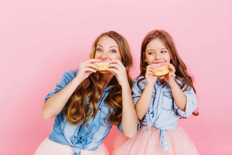 happy young mother and daughter eating donuts
