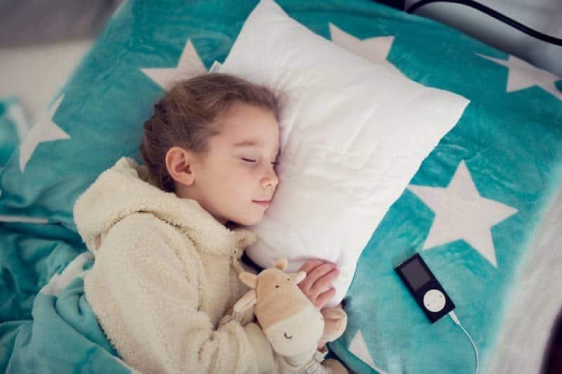Little girl listening to music before sleeping