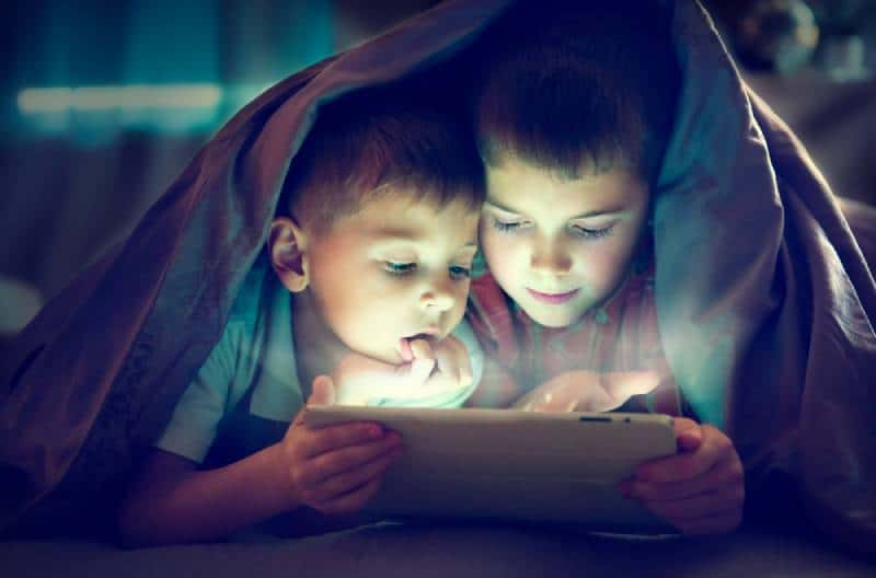 Two kids using tablet pc under blanket at night