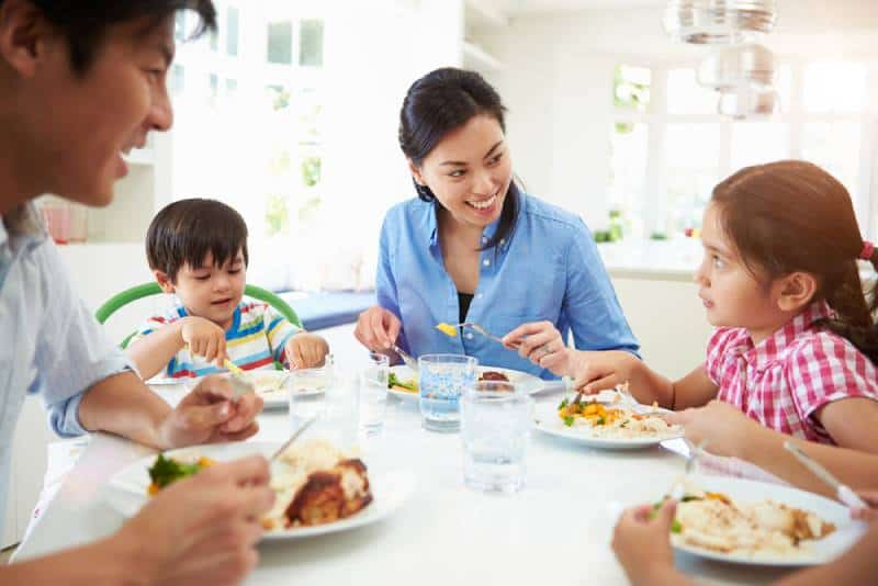 Family Sitting At Table Eating Meal Together