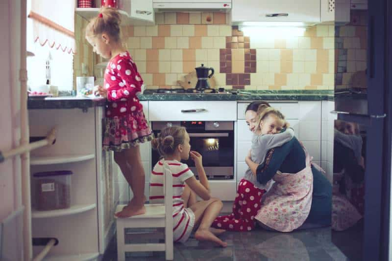 Mother hugging child in the kitchen