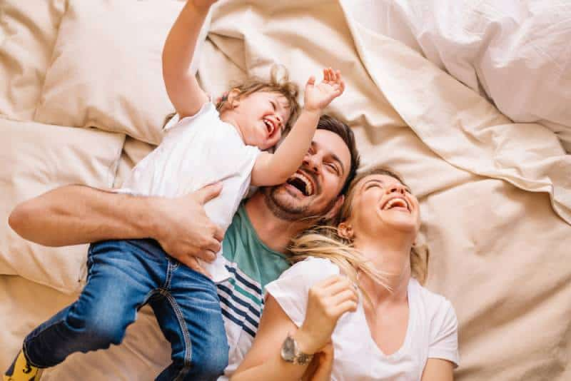 family laughing while they lie on bed