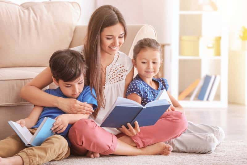 woman and her little children reading books at home