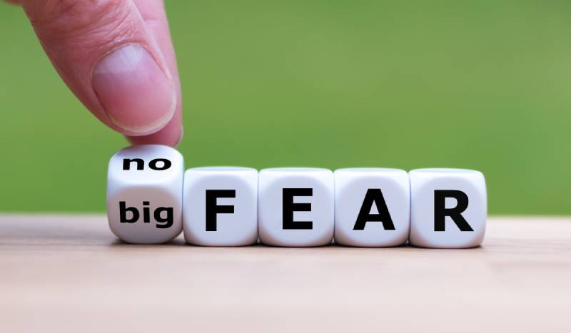 "Hand turns a dice and changes the expression ""big fear"" to ""no fear"""
