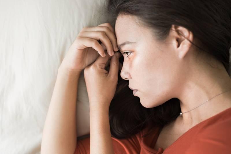 Sad woman in orange shirt lying in bed