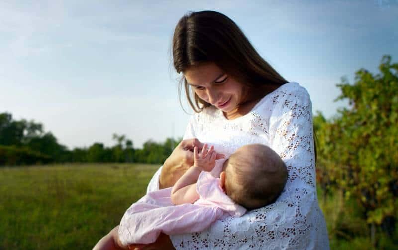 Woman breastfeeding her newborn baby girl in the park
