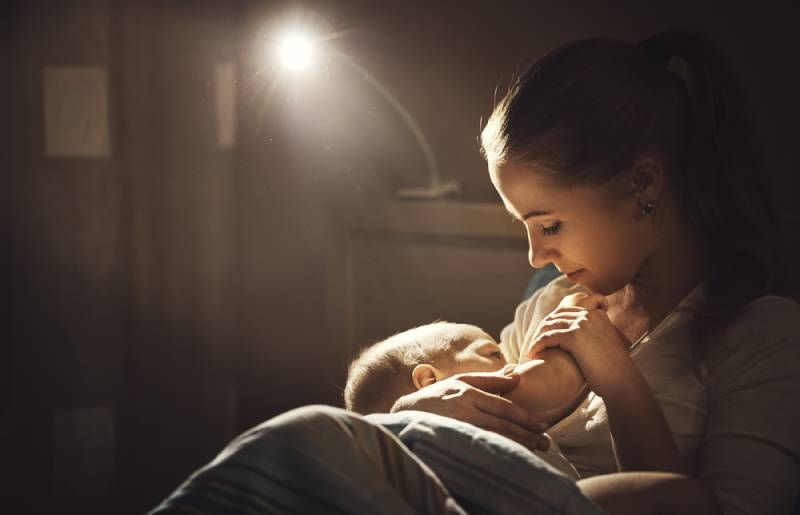 mother breastfeeds the baby in the evening
