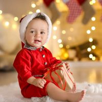 baby in christmas suit with gift