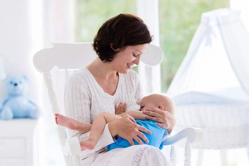 woman sitting on bed and breastfeeding her baby