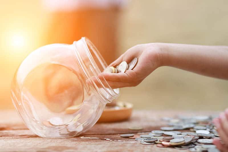 Woman's hand where she puts money in saving jar
