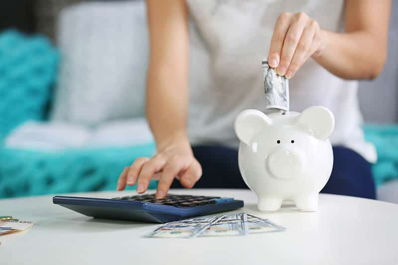 Woman is saving some money by putting it into piggy bank at her home