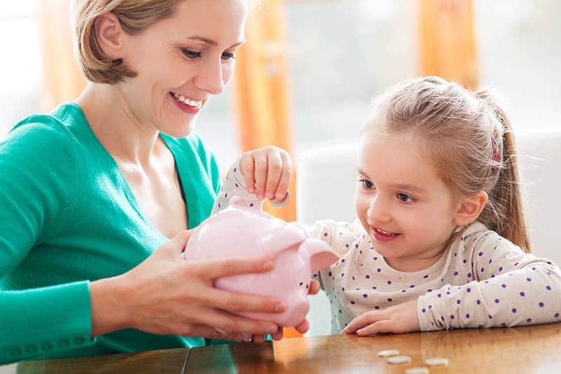 Woman holding piggy bank and daughter putting money in it