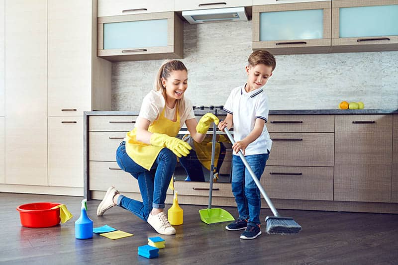 child doing chores while mom is being with him