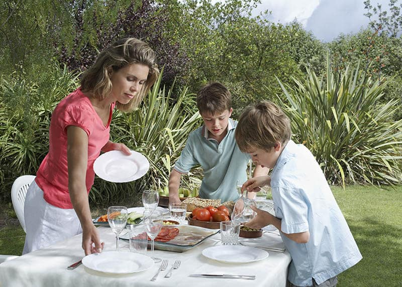 Kids help mom with serving lunch outdoors