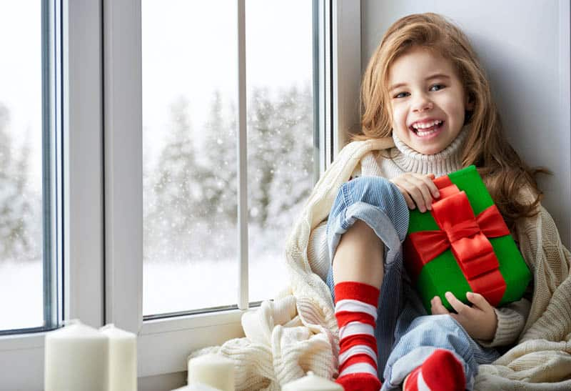 beautiful little girl posing with gift in hands
