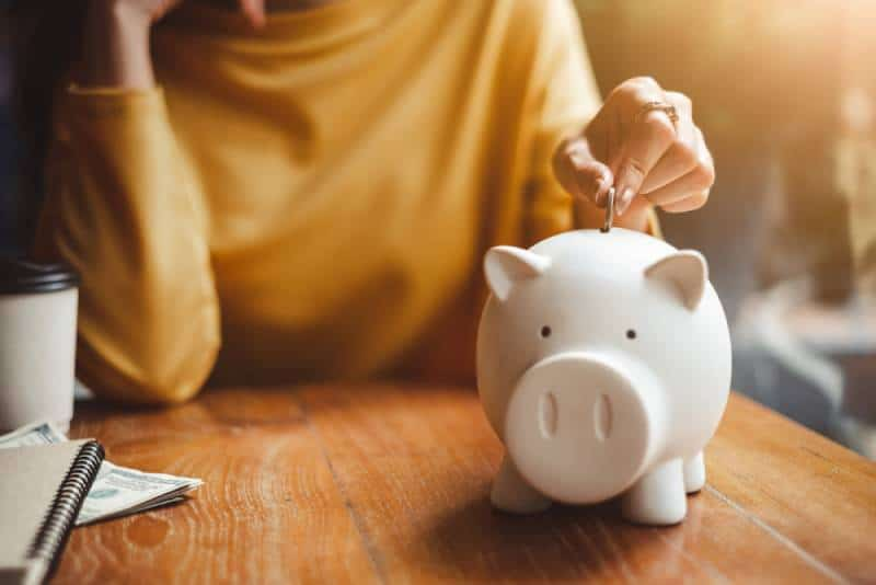 woman hand putting money coin into piggy for saving money