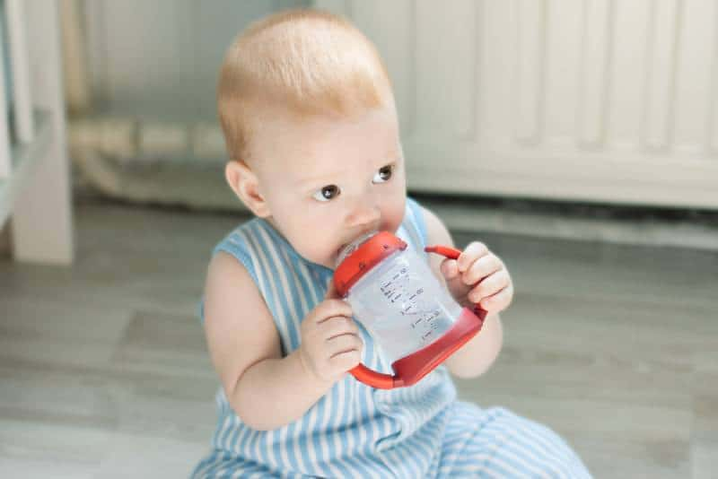 Baby boy drinking from baby cup and sitting on floor