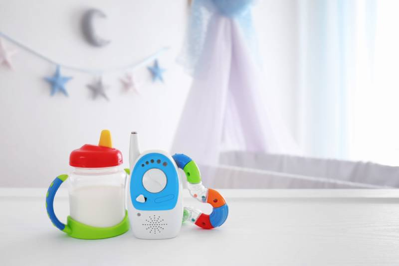 Baby monitor, rattle and sippy cup on table in room