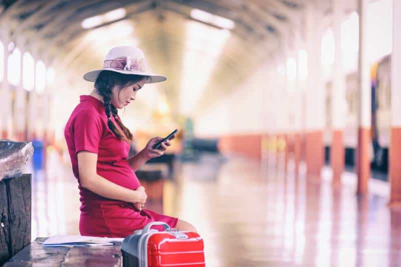 Pregnant woman with a suitcase waiting for the train