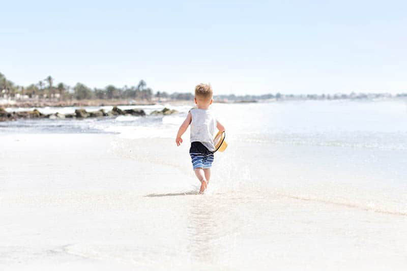 Little boy walking on the beach holding a hat