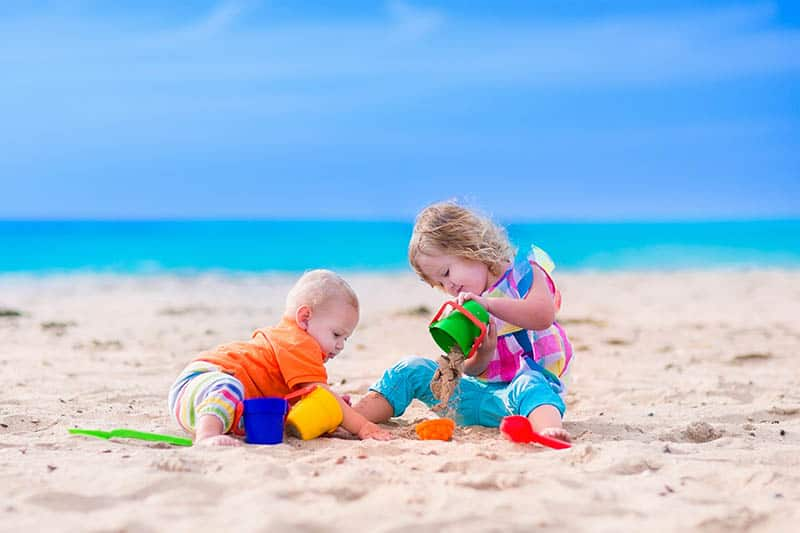 Toddler and a baby playing with sand