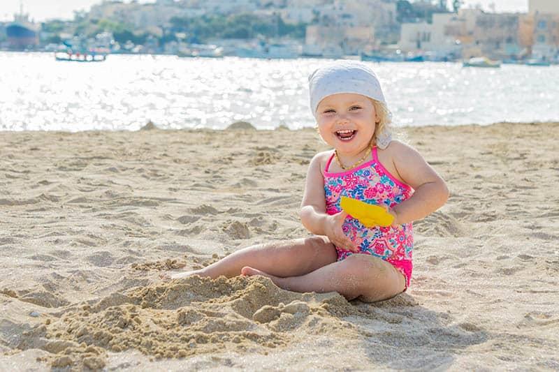 Little happy girl sitting on the beach
