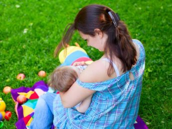 Woman breastfeeding child outside