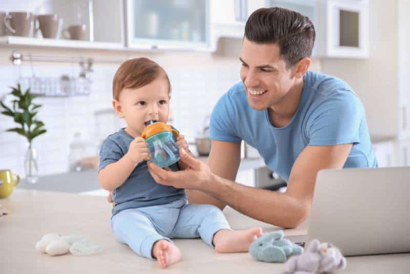Young dad giving water in a sippy cup to his little son at home
