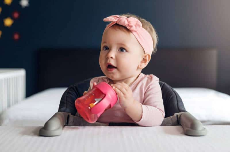 baby girl holding a sippy cup