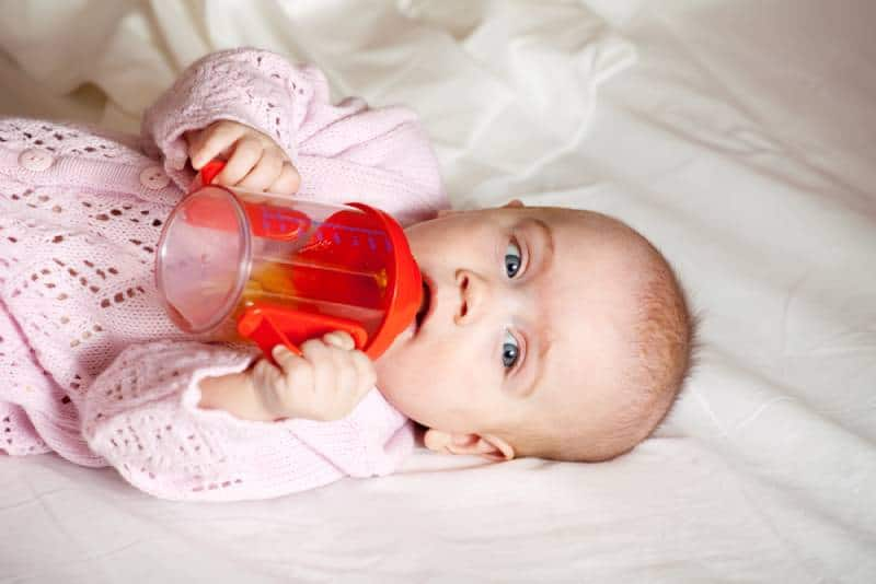 baby girl with sippy cup lying on blanket