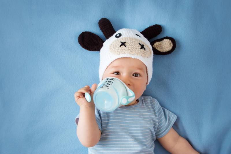 cute baby in a cow hat drinking from a sippy cup