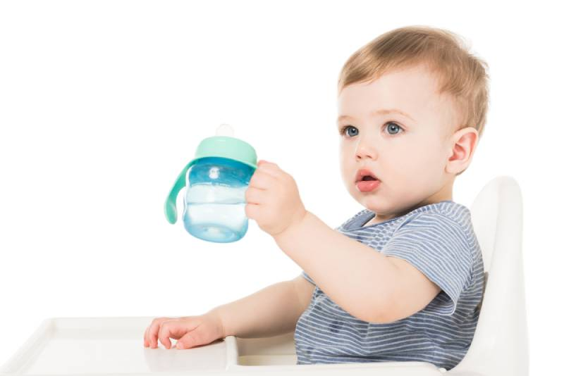 little boy holding baby cup with water