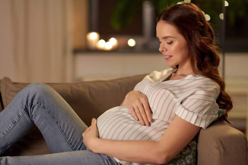 pregnant woman resting on the couch at night