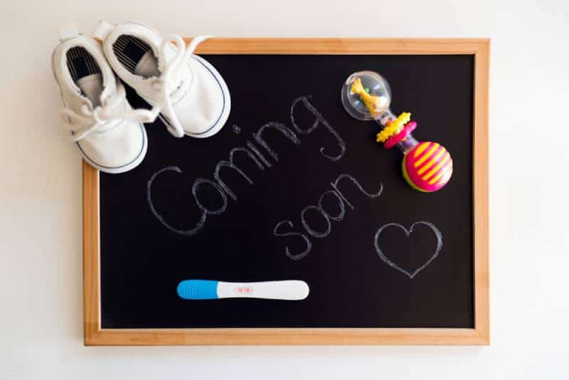 Coming soon words on black chalkboard with positive pregnancy test