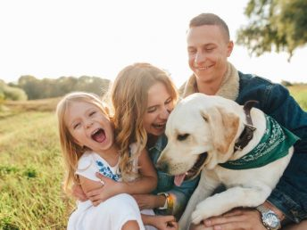 Mom, dad, and daughter with a dog