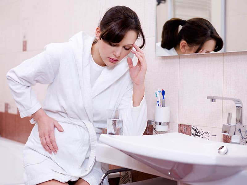 Pregnant woman in bathroom feeling sick