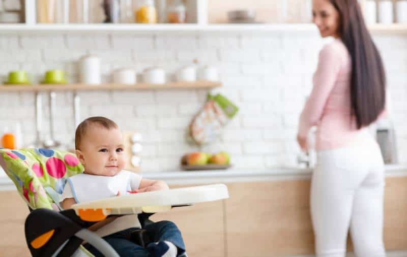 baby playing on high chair in the kitchen