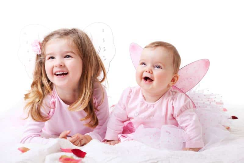 Little sisters wearing fairy wings