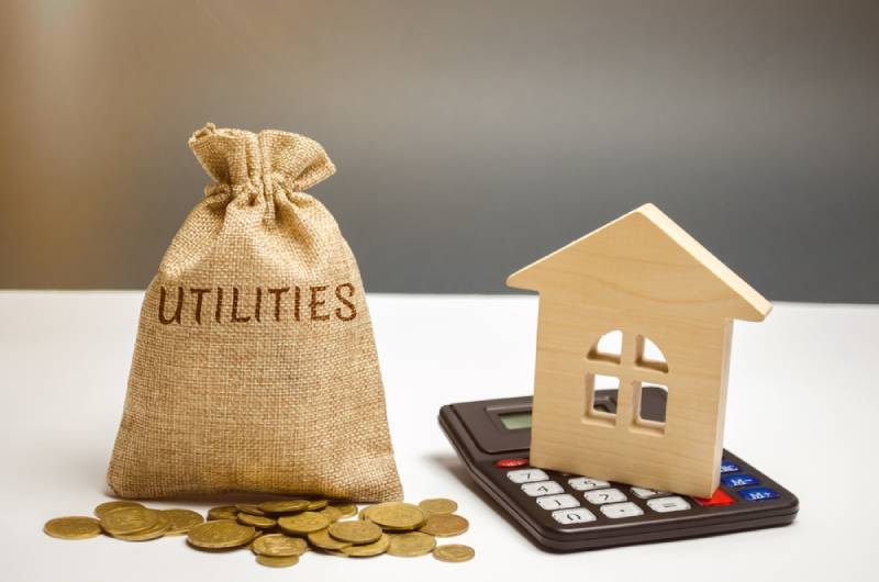 money bag with the word Utilities and a wooden house