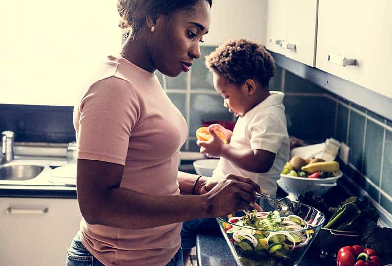 mother making salad with baby boy in the kitchen