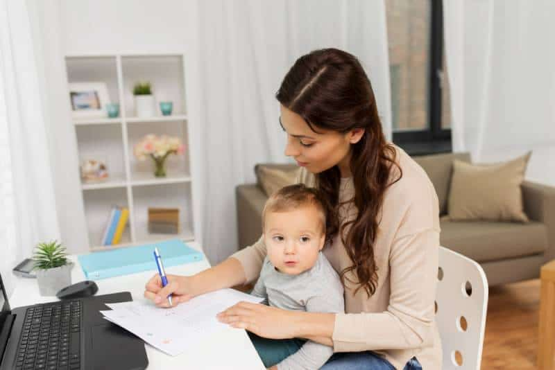 mother with baby, papers and laptop working at home