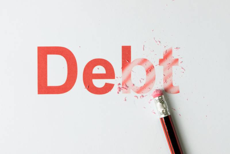 pencil erasing the word debt on paper