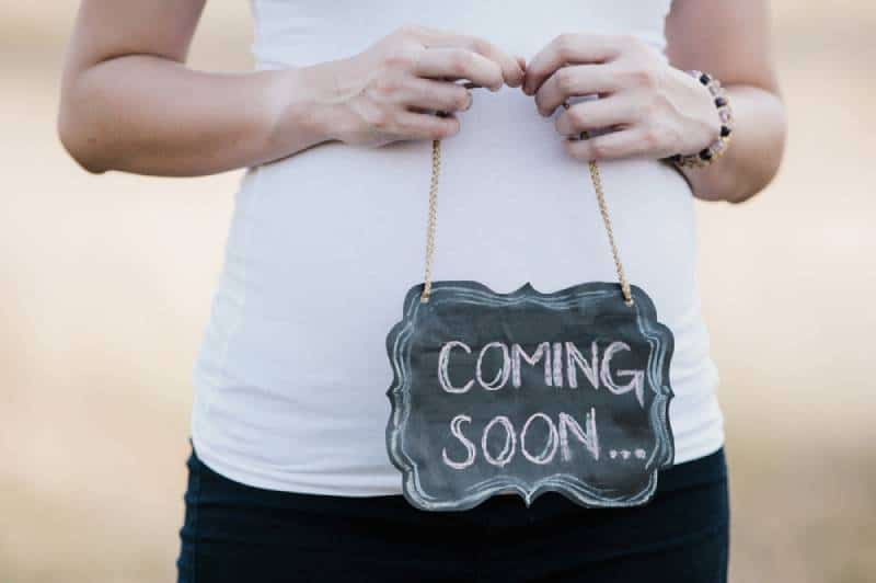 pregnant woman holding coming soon chalkboard sign