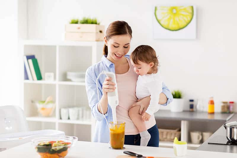 woman making baby food while holding baby in hand