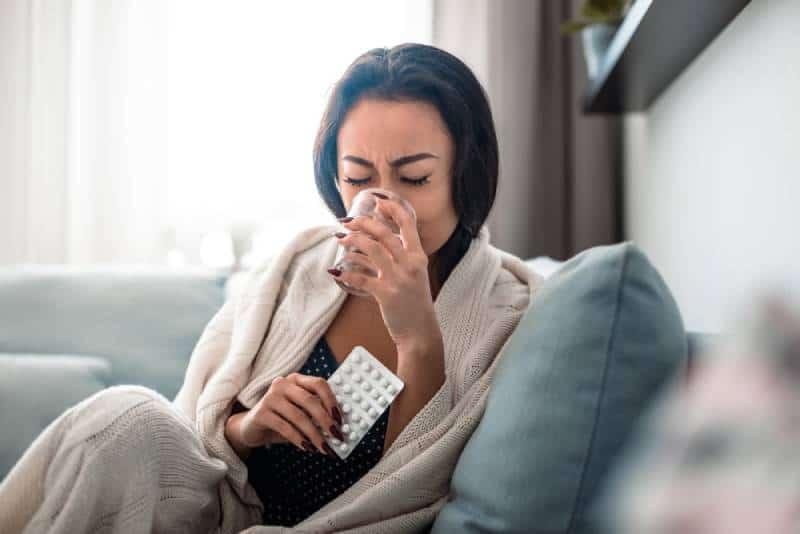 Woman taking medication pills