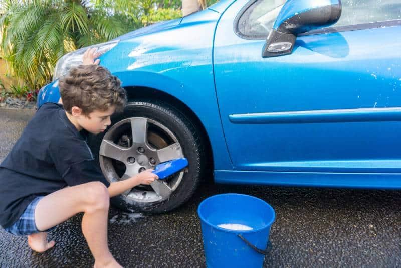 Boy earning pocket money - washing a car